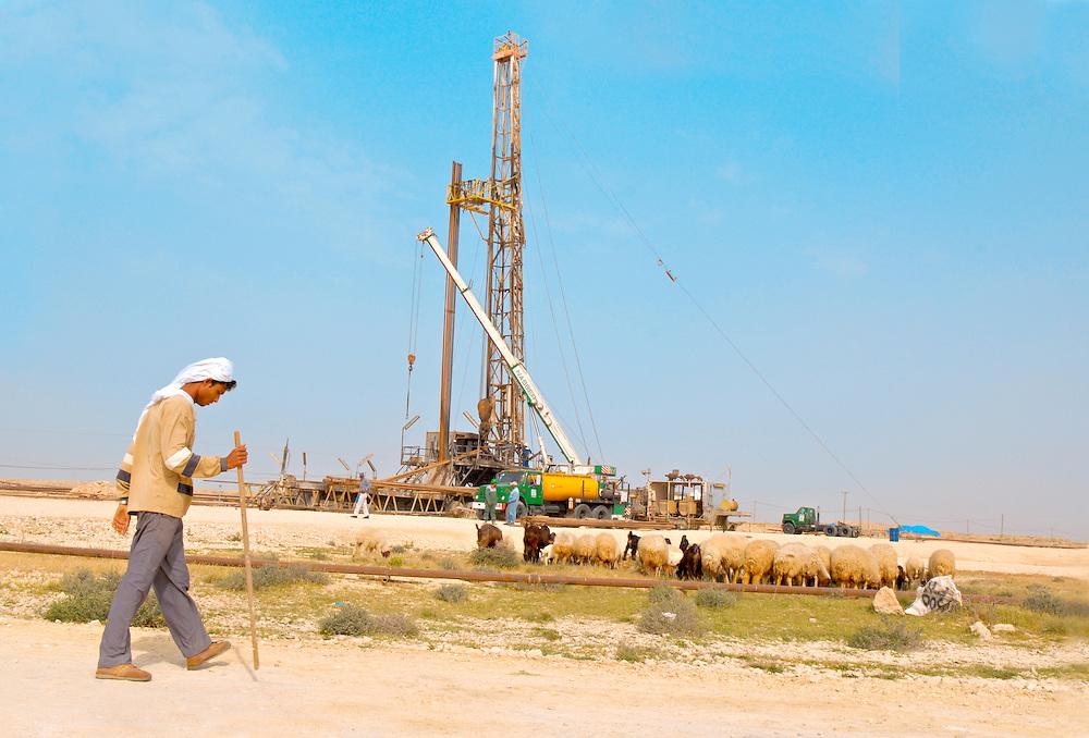 Bahrain; Wüste Ein Scäfer zieht mit seiner Schafheerde an einer Erdölplattform vorbei