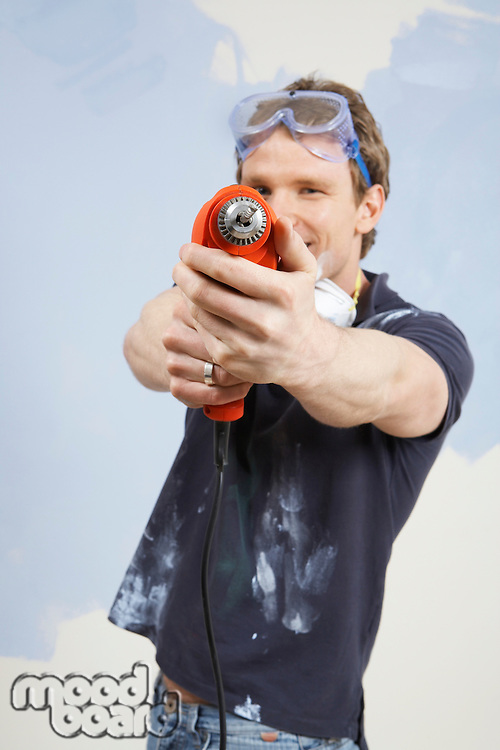 Man pointing drill in front of half painted wall portrait