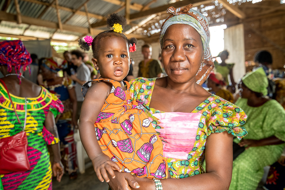 A woman holds a child at a church service in Ganta, Liberia