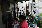 SELMA, AL – MAY 15, 2014: Raven, age 3, sits with her family on the front porch of their home. Her grandmother, Charity Baskin, is unemployed and unable to work because of back trouble. Dallas County has one of Alabama's highest unemployment rates, and in recent months the prospect of a plan to to begin training Kuwaiti pilots in an old military airport is offering new hope for Selma's residents. CREDIT: Bob Miller for The New York Times