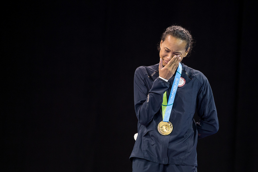 Gold medalist  Paige McPherson of the United States weeps as the national anthem plays during the medal ceremony for the women's taekwondo -67 kg division at the 2015 Pan American Games in Toronto, Canada, July 21,  2015.  AFP PHOTO/GEOFF ROBINS
