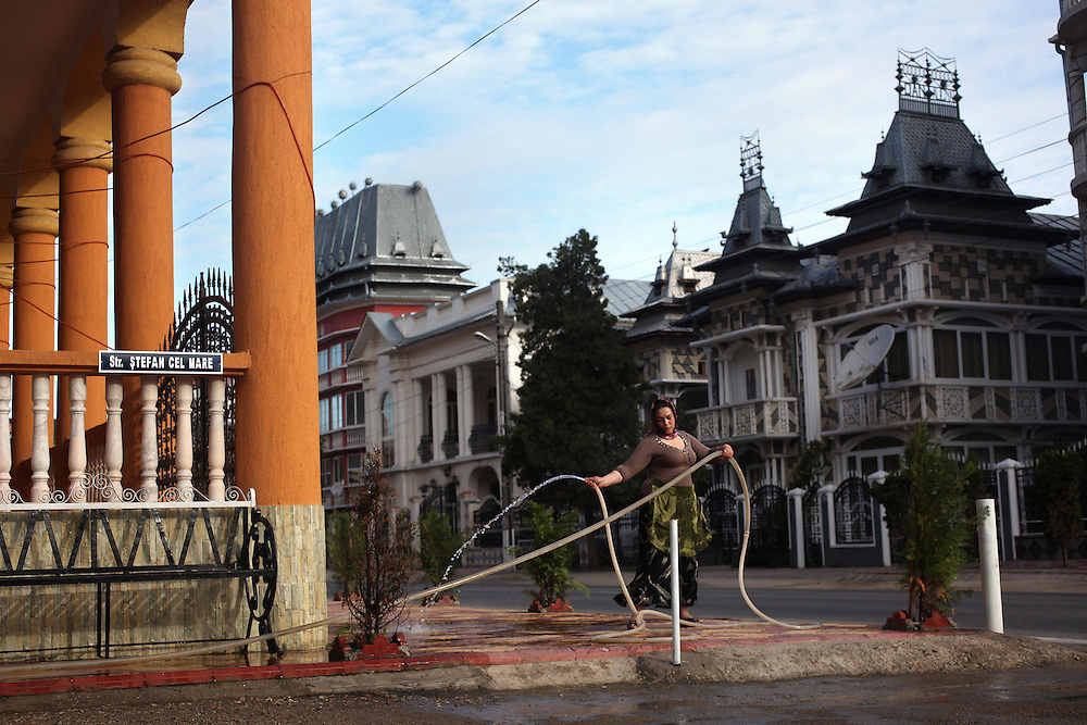 A Roma woman cleans the sidewalk outside her house using a hose in Buzescu, Romania. <br /> <br /> Home of the Wealthy Roma (Summary):  Richly adorned multi-story mansions with elaborate turrets, balconies, pillars and adornments from across the history of architecture are not the first thing that springs to mind when one thinks of Roma, or Gypsies as they are disparagingly known across Europe. Yet in Buzescu, a small town of 5,000 inhabitant 50 miles southwest of Bucharest, the Romanian capital, the main street is lined with a most unlikely row of architectural adventures in a strange catalogue of pastel colours and oddly combined materials. On the streets between these clusters of gaudy castles, fleets of Mercedes slowly move over rutted streets. A third of Buzescu's inhabitants are Roma yet the ostentatious construction style dominates large parts of the town and challenges the received perception of Roma being a poor, itinerant lot, wandering through the countryside incessantly without putting down roots. Buzescu's Roma, most of whom are Kalderash or 'coppersmiths', are well known for their craftsmanship in making cazane, a traditional copper still used in making fruit brandy and the best craftsmen could fetch very respectable fees for their handmade cazanes. It was after the end of the communist regime in Romania, though, that the entrepreneurial spirit of the Kalderash came into its own. With industrial infrastructure being left to rot across the country and Eastern Europe, astute Roma were quick to realise the potential in the copper, silver, aluminium, steel and other scrap metals that were there for the taking. Many Roma were able to reap handsome profits in the unregulated commodity markets of the early post-communist era. The show of wealth in Buzescu is mainly for local consumption, and much of it remains on the exterior. Many of the villas still have outhouses and remain sparsely furnished inside. But the town has become a curious showcase of the contemporary self-