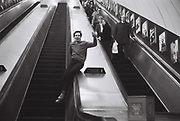 Teenager slides down the escalator at bond street station watched by other tube. London, UK, 1980s.