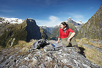 Woman sitting with laptop on mountain peak