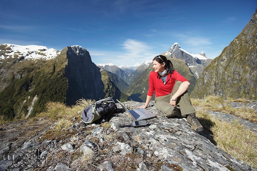 Woman sitting with laptop on mountain peak