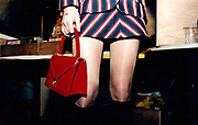 Waist down view of a young woman wearing a striped mini skirt and carrying a red handbag.
