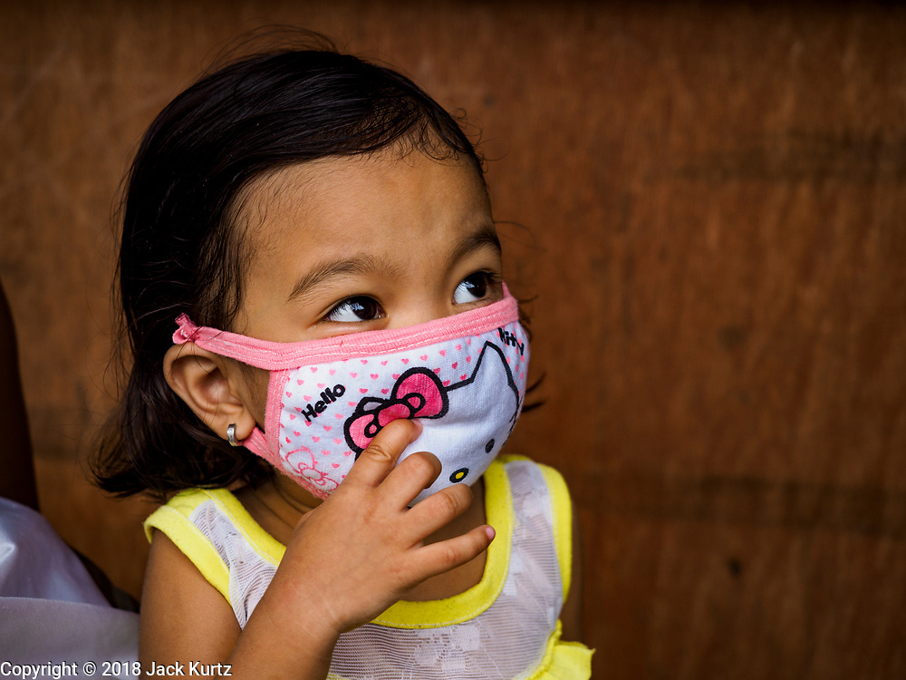 "22 JANUARY 2018 - GUINOBATAN, ALBAY, PHILIPPINES: A child in Guinobatan wears a face mask because of an ash fall caused by the eruption of Mayon volcano. Several communities in Guinobatan were hit ash falls from the eruptions of the Mayon volcano and many people wore face masks to protect themselves from the ash. There were a series of eruptions on the Mayon volcano near Legazpi Monday. The eruptions started Sunday night and continued through the day. At about midday the volcano sent a plume of ash and smoke towering over Camalig, the largest municipality near the volcano. The Philippine Institute of Volcanology and Seismology (PHIVOLCS) extended the six kilometer danger zone to eight kilometers and raised the alert level from three to four. This is the first time the alert level has been at four since 2009. A level four alert means a ""Hazardous Eruption is Imminent"" and there is ""intense unrest"" in the volcano. The Mayon volcano is the most active volcano in the Philippines. Sunday and Monday's eruptions caused ash falls in several communities but there were no known injuries.    PHOTO BY JACK KURTZ"