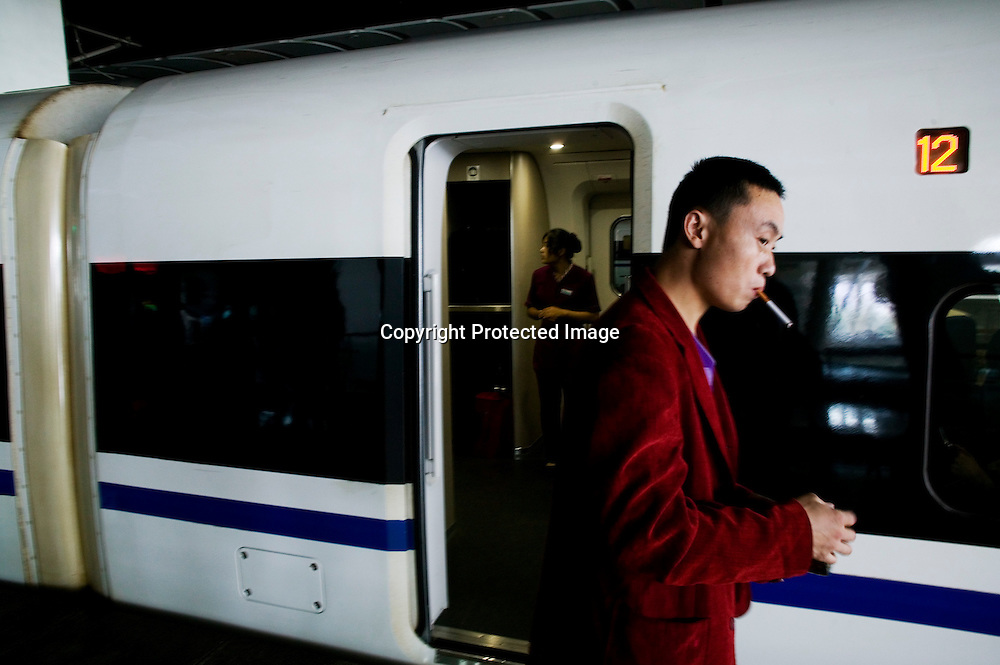 Beijing, September 11 , 2011 :a man smokes a cigerette minutes before the journey to Shanghai starts. the passenger-dedicated trunk line opened in June 2011, reducing the 1,318 km journey between Beijing and Shanghai to less than 5 hours. Trains reach top speeds of 300 km/h (186 mph) for the entire trip.