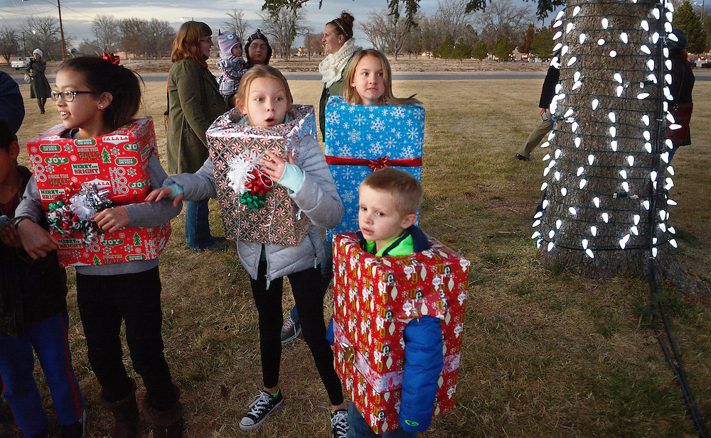 gbs120116b/ASEC -- Dressed in present costumes,Alexis Potter, 9, Kaylee Phillips, 9, Alexis Goggin, 11, and Aiden Cole, 6, from the Kirtland Air Force Base Youth Center, spot Santa's arrival at the Base tree lighting ceremony on Thursday, Dec. 1, 2016. The annual ceremony features Santa Claus, caroling and refreshments.(Greg Sorber/Albuquerque Journal)