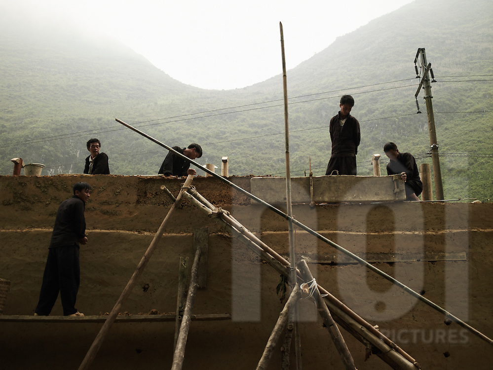 A group of men build a house with rammed earth walls. Ha Giang province, Vietnam, Asia