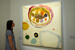 "© Licensed to London News Pictures. 17/07/2019. LONDON, UK. A staff member views ""Snare"", 1962, by Gillian Ayres at the preview of ""Brave New Visions: The Émigrés who transformed the British Art World"", a new exhibition at Sotheby's gallery in New Bond Street which runs 17 July to 9 August 2019.  The show is also part of ""Insiders / Outsiders"", a nationwide, year long festival celebrating refugees from Nazi Europe and their contribution to British culture.  Photo credit: Stephen Chung/LNP"