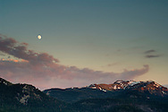Moon rising over clouds and mountains at sunset, from Echo Summit, near Lake Tahoe, California