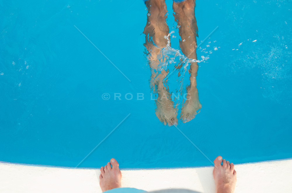 detail of two men's feet at a swimming pool
