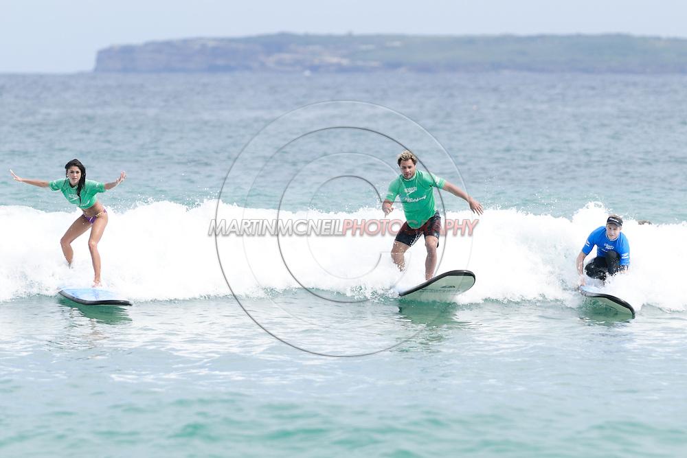 SYDNEY, AUSTRALIA, FEBRUARY 25, 2011: Arianny Celeste and Josh Koscheck ride the surf on Bondi Beach in Sydney, Australia on February 25, 2011.