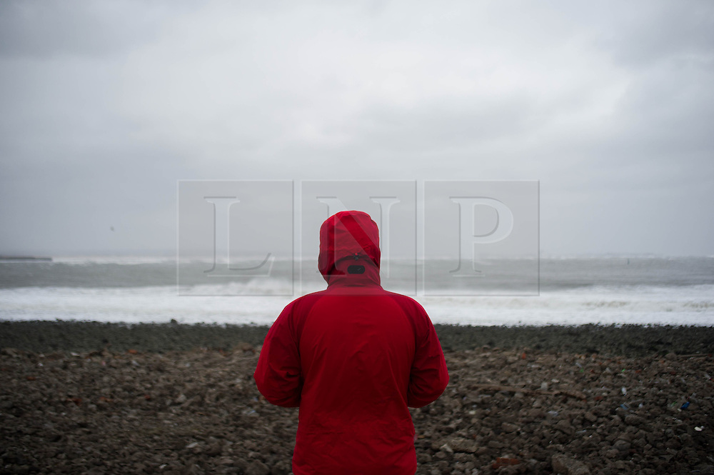 © Licensed to London News Pictures. 23/03/2013..Cleveland, England..A man checks the surf conditions as the wintery weather continues to chill the country. Cleveland on the east coast of England suffered freezing cold temperatures and strong winds that brought big seas to the coastline...Photo credit : Ian Forsyth/LNP