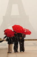 eiffel tower and red umbrellas during a hail storm