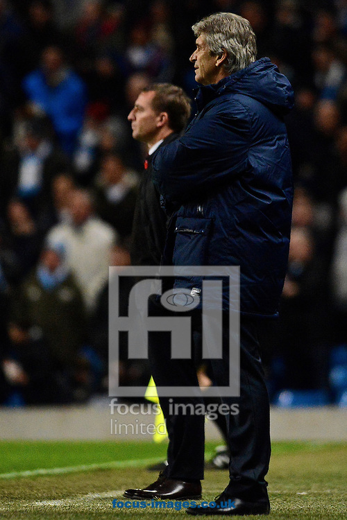 Picture by Ian Wadkins/Focus Images Ltd +44 7877 568959<br /> 26/12/2013<br /> Manchester City manager Manuel Pellegrini (foreground) and Liverpool manager Brendan Rodgers during the Barclays Premier League match at the Etihad Stadium, Manchester.