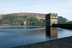 "Derwent Reservoir in Derbyshire, England is the middle of three reservoirs in the Upper Derwent Valley, the higher reservoir being Howden to the North and the lower being Ladybower to the south. Between them they provide practically all of Derbyshire's water, as well as to a large part of South Yorkshire and as far afield as Nottingham and Leicester.<br /> Begun in 1902 this neo-Gothic solid masonry dam wall is built from huge stones that were transported along a specially created railway from the quarries at Grindleford. Over 1,000 workers lived in a specially constructed and self-contained town of Birchinlee also known as ""Tin Town"". Derwent reservoir began being filled in November 1914, and overflowed for the first time in January of 1916. Covering an area of 70.8 hectares (175 acres) and at its deepest point is 34.7 metres (114 ft) the dam can support a total of 9.64 million cubic metres of water.<br /> For 6 weeks during the Second World War the reservoir was used by the pilots of the 617 Squadron ""the Dambusters"" to practice their low-level flying skills needed for Operation Chastise, because of the Derwents similarity to the operations German target. In for 2 weeks in 1954 the the sound of Lancaster bomber engines could be heard again over the Derwent as the reservoir stood in for the German dams a second time. This time for the filming of the ""The Dambusters"" starring Richard Todd as Guy Gibson. The west tower of the dam wall is home to Derwent Valley Museum and includes a permanent memorial to 617 Squadron to which is visible even when the Museum is closed. <br /> <br /> 22  March 2015 Image © Paul David Drabble www.pauldaviddrabble.co.uk"