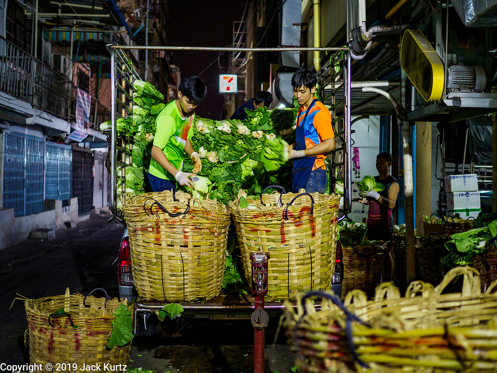 27 FEBRUARY 2019 - BANGKOK, THAILAND: Men working the overnight shift sort lettuce in a Bangkok vegetable market. Bangkok, a city of about 14 million, is famous for its raucous nightlife. But Bangkok's real nightlife is seen in its markets and street stalls, many of which are open through the night.       PHOTO BY JACK KURTZ