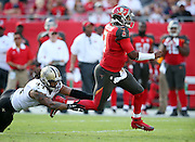 Tampa Bay Buccaneers quarterback Jameis Winston (3) runs away from a shoestring tackle attempt by New Orleans Saints rookie outside linebacker Hau'oli Kikaha (44) for a gain of 18 yards and a first down inside the Saints 25 yard line in the second quarter during the 2015 week 14 regular season NFL football game against the New Orleans Saints on Sunday, Dec. 13, 2015 in Tampa, Fla. The Saints won the game 24-17. (©Paul Anthony Spinelli)