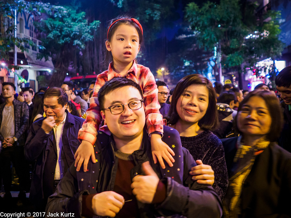 24 DECEMBER 2017 - HANOI, VIETNAM:  People watch the Christmas Eve celebration at St. Joseph's Cathedral in Hanoi. The commercial and gift giving aspect of Christmas is widely celebrated in Vietnam and Vietnam's 5+ million Catholics celebrate the religious aspects of Christmas.    PHOTO BY JACK KURTZ