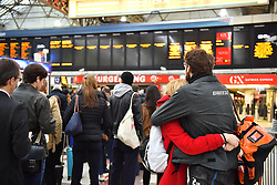 © Licensed to London News Pictures. 14/12/2016. London, UK.  Two passengers embrace while looking at departure boards at Victoria Station in London on 14 December 2016, as hundreds of thousands of rail passengers face a second day of a 3 day all-out strike in an escalating dispute over the role of conductors between Southern Rail and the RMT Union. Photo credit: Ben Cawthra/LNP