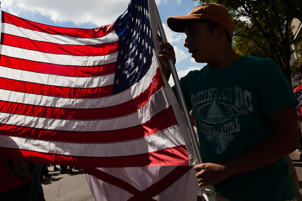 BIRMINGHAM, AL – OCTOBER 5, 2013: Brandon Vela, 15, carries the American flag during a march organized by the Alabama Coalition for Immigrant Justice. The march was held to draw attention to the need for immigration reform in Congress. CREDIT: Bob Miller for The New York Times