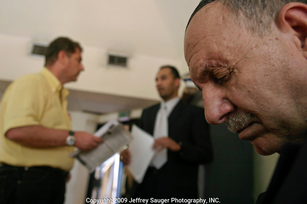Emad Al-kasid posts a press release for the media as his father Malik Al-Kasid looks around the Palestine Hotel in Baghdad, Iraq, Tuesday, July 22, 2003. The press release is about the family travelling back to its home in Nassiriyah, Iraq, for the first time since 1991 after fighting in the failed uprising against Saddam Hussein, fleeing to a refuge camp in Saudi Arabia for 3 years and finally settling in Dearborn, MI.Malik Al-kasid is the chief of the Hacham Al-kasid tribe and Emad is the U.S. spokesman. Nassiriyah continues to be one of the most organized and safest states in Iraq.