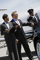 Mid-adult businesswoman, senior businessman and chauffeur in front of car.