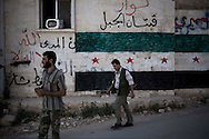 Syria. Syrians men walk in front of a mosque painted with the colors of the old Syrian flag in Aleppo's province. ALESSIO ROMENZI