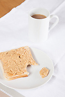 Coffee mug and peanut butter on wheat bread
