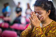 31 MARCH 2013 - BANGKOK, THAILAND:     Dachanee (Kaew) Ariso prays during Easter services at the Thai Peace Foundation office in the Bangkapi section of Bangkok.     PHOTO BY JACK KURTZ