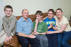 Mother and father relaxing at home with their three sons who have Autism,