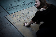 Los Angeles, April 2012 - A fan posing for a picture with the handprint of Marilyn Monroe in front of the Graumanâs Chinese Theater.
