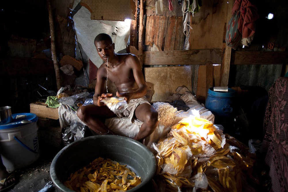 Michelot Groshomme puts fried plantain chips into bags.  He fries the plantain chips in front of his tent and stores them in his tent that he shares with five others. He sells the chips for 10 gourdes (0.25 USD) on the side of the road.