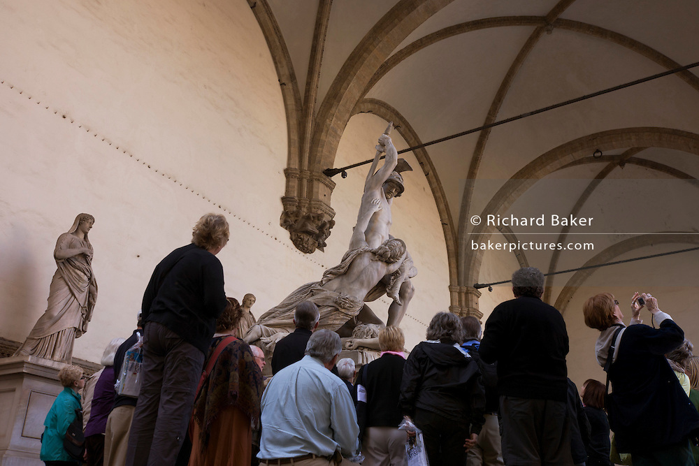 A European tour group admires renaissance statue copies in Florence's Loggia dei Lanzi, Piazza della Signoria. Standing beneath the taller piece entitled 'Rape of the Sabine Women' is by the Flemish artist Jean de Boulogne, better known by his Italianized name Giambologna and the visitors to this medieval city tour the cultural landmarks beneath gothic arches and replica artworks. The Rape of the Sabine Women is an episode in the legendary history of Rome in which the first generation of Roman men acquired wives for themselves from the neighboring Sabine families. The Loggia dei Lanzi, also called the Loggia della Signoria, is a building on a corner of the Piazza della Signoria adjoining the Uffizi Gallery. It consists of wide arches open to the street, three bays wide and one bay deep.