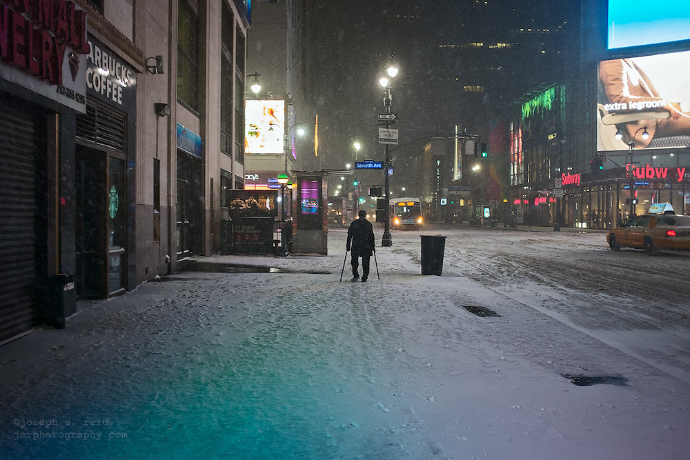 Man with canes walking along West 34th Street in snow storm at night, New York, NY, US