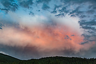 Dramatic breaking storm catches the light of sunset above forested mountains, Jemez Mountains, NM, © 2010 David A. Ponton