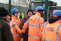 Harefield, UK. 8 February, 2020. HS2 engineers link arms to block environmental activists who had crawled through a ditch under a road closure implemented by HS2 engineers on Harvil Road in the Colne Valley to facilitate tree felling works for the high-speed rail project. Environmental activists based at a series of wildlife protection camps in the area prevented the tree felling works for the duration of the weekend for which they were scheduled.