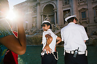 """ROME, ITALY - 20 JUNE 2017: A Roman policewoman and policeman, entrusted to protect the Fountain of Trevi, is seen here by the fountain in Rome, Italy, on June 20th 2017.<br /> <br /> The warm weather has brought a menacing whiff of tourists behaving badly in Rome. On April 12, a man went skinny-dipping in the Trevi fountain resulting in a viral web video and a 500 euro fine.<br /> <br /> Virginia Raggi, the mayor of Rome and a national figurehead of the anti-establishment Five Star Movement,  issued an ordinance involving harsher fines for eating, drinking or sitting on the fountains, for washing animals or clothes in the fountain water or for throwing anything other than coins into the water of the Trevi Fountain, Bernini's Four Fountains and 35 other city fountains of artistic or historic significance around the city.  """"It is unacceptable that someone use them to go swimming or clean themselves, it's an historic patrimony that we must safeguard,"""" Ms. Raggi said."""