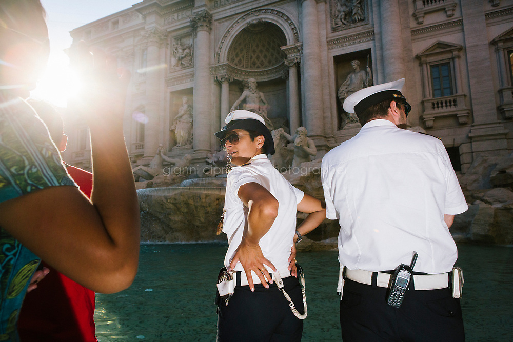 ROME, ITALY - 20 JUNE 2017: A Roman policewoman and policeman, entrusted to protect the Fountain of Trevi, is seen here by the fountain in Rome, Italy, on June 20th 2017.<br /> <br /> The warm weather has brought a menacing whiff of tourists behaving badly in Rome. On April 12, a man went skinny-dipping in the Trevi fountain resulting in a viral web video and a 500 euro fine.<br /> <br /> Virginia Raggi, the mayor of Rome and a national figurehead of the anti-establishment Five Star Movement,  issued an ordinance involving harsher fines for eating, drinking or sitting on the fountains, for washing animals or clothes in the fountain water or for throwing anything other than coins into the water of the Trevi Fountain, Bernini&rsquo;s Four Fountains and 35 other city fountains of artistic or historic significance around the city.  &ldquo;It is unacceptable that someone use them to go swimming or clean themselves, it&rsquo;s an historic patrimony that we must safeguard,&rdquo; Ms. Raggi said.