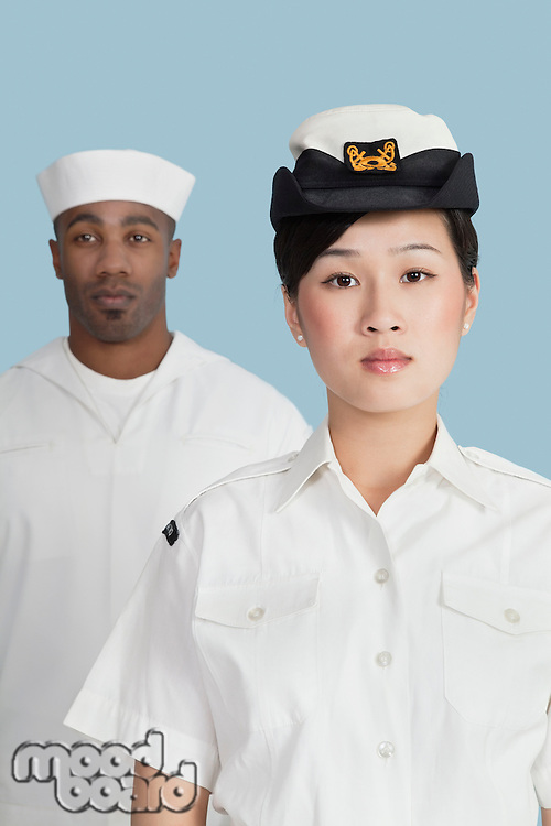 Portrait of serious female US Navy officer in front male sailor over light blue background