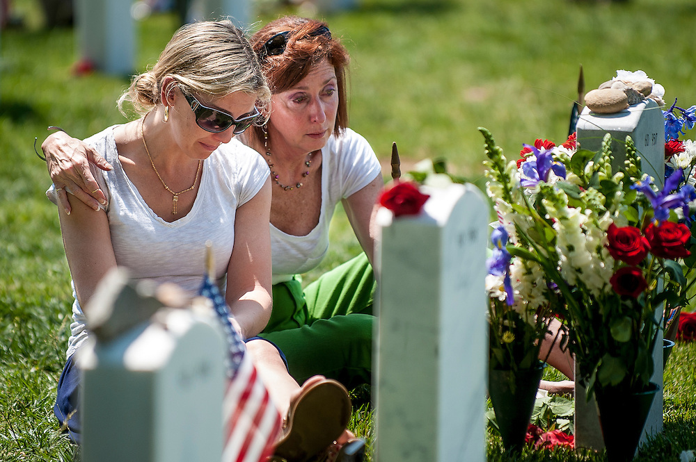Janice Bryant of Arlington, VA and USAF Lt. Col. Sally Stenton of Cherry Hill, NJ, sit at the headstone of Bryant's husband, USAF Lt. Col. Frank Bryant Jr. onMemorial Day at Arlington National Cemetery in Arlington, VA, USA on 28 May, 2012.