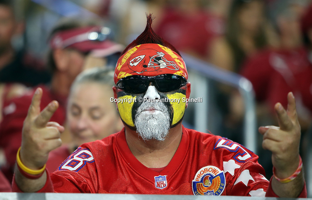 A Kansas City Chiefs fan with sunglasses, a pointed hairdo, and painted face gives the victory sign during the 2015 NFL preseason football game against the Arizona Cardinals on Saturday, Aug. 15, 2015 in Glendale, Ariz. The Chiefs won the game 34-19. (©Paul Anthony Spinelli)