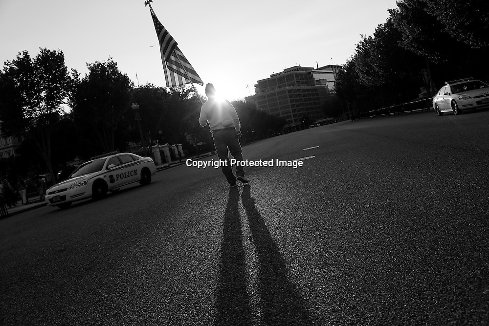American Legion member William Szych, of Virginia, carries a U.S. national flag on Pennsylvania Avenue in front of the White House, to demand that all U.S. war memorials remain open during the government shutdown, in Washington, October 4, 2013. Washington headed into the fifth day of a partial government shutdown with no end in sight even as another, more serious conflict over raising the nation's borrowing authority started heating up.