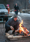 em122415h/jnorth/Manny Morales, forground and Julien Ross get a fire going to warm themselves and other people walk along the Delgado Street on Christmas Eve in Santa Fe, Thursday December 24, 2015. (Eddie Moore/Albuquerque Journal)
