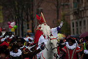 Saint Nicolas arrrives during the Sinterklaas parade, Dam Square, Amsterdam, 14th November 2010. Sinterklaas, the basis for Santa Claus in other countries, arrives from Spain by boat,  accompanied by Black Peter, played by multitudes of white Dutch people in blackface - a tradition that evokes some controversy. Contrary to traditions of Santa Claus elsewhere, Sinterklass arrives by boat, then rides through the streets on his grey horse, Amerigo,  in mid-November, bringing in the Christmas season. The Zwarte Pieten (Black Peters) distribute sweets and gingerbread cookies to the crowd along the parade route.