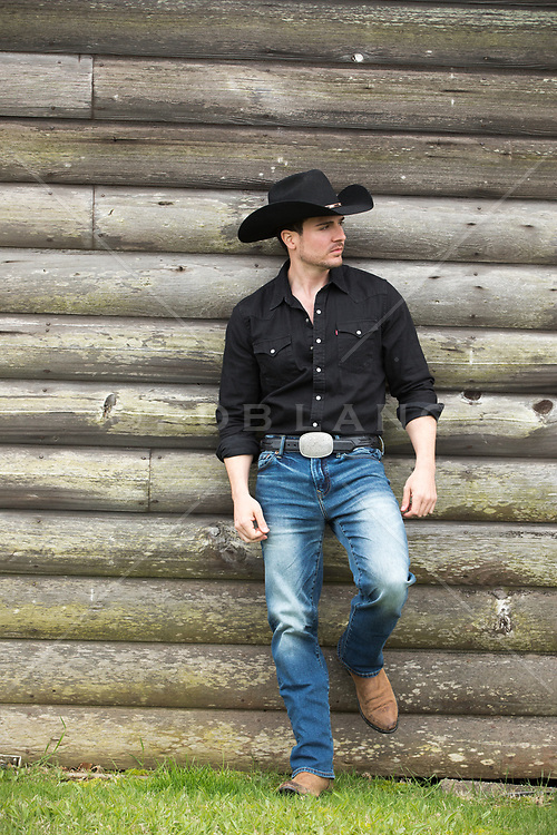 cowboy leaning against a rustic cabin