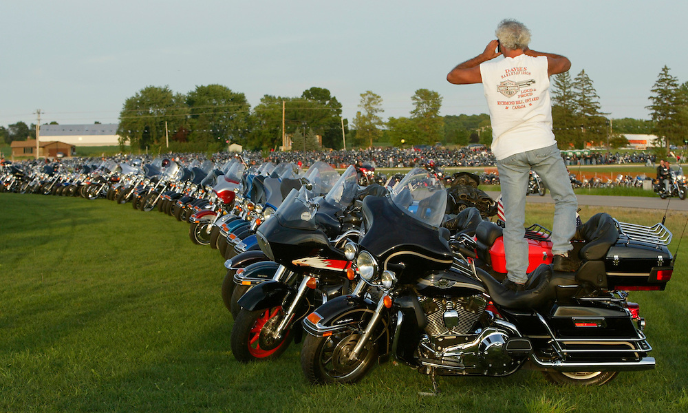 Dave Haney of Toronto, Canada stands on his Harley Davidson to shoot a picture of the motorcycles at the HOG XX party in West Bend, Wisconsin celebrating the 100th anniversary of Harley Davidson in nearby Milwaukee August 27, 2003.  Haney rode his 2003 Ultra Classic from Toronto for the event. REUTERS/Rick Wilking