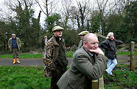 Fox Hunting.Stratfield, Hampshire, England, February 2nd, 2005 - Foot followers staring at field while Vale of Aylesbury with Garth and south hunt pack passing by.